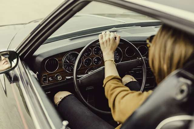 Woman with sore throat driving car